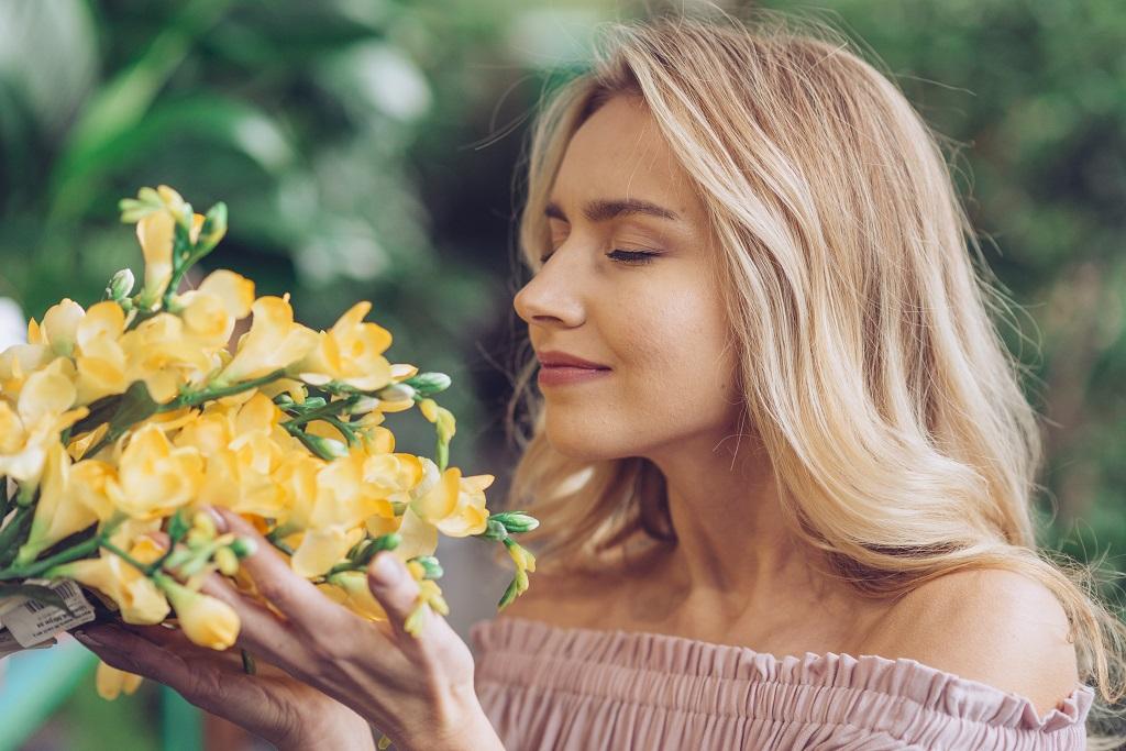 beautiful women smells bouquet of fresh yellow flowers