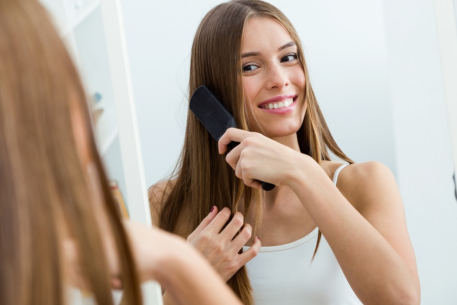 Beautiful young woman brushing her long hair