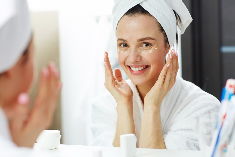 young woman uses moisturizer after shower