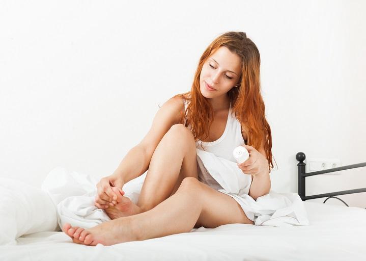 girl applying moisturizer to her legs