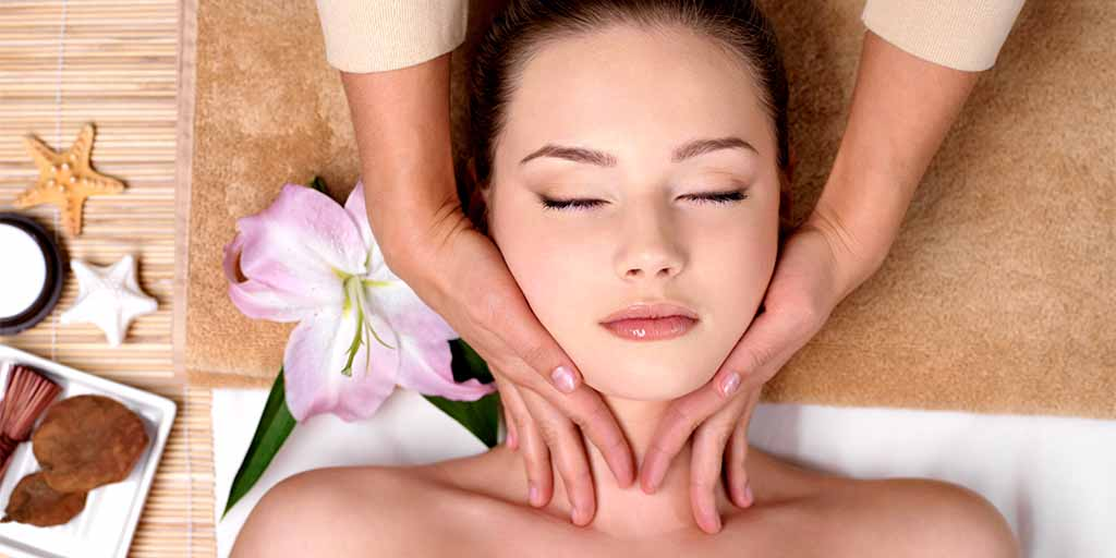 Beautiful young girl getting massage for neck in spa salon