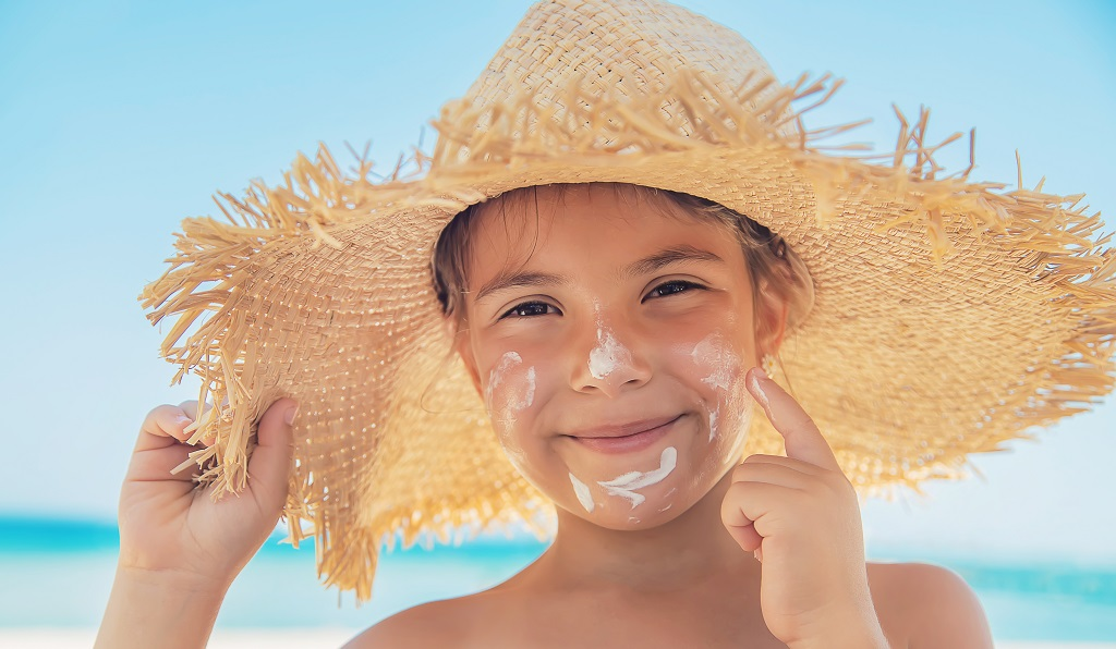 young girl putting sunscreen on