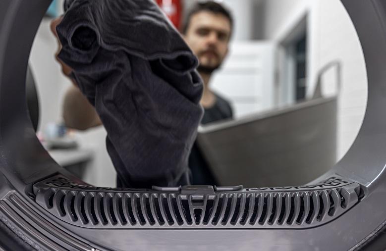 man putting his laundry into a washing machine